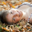 Happy girl lies in oak leaves — Stock Photo
