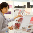Girl is buying lipstick — Stock Photo