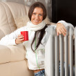 Woman near oil heater — Stockfoto