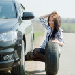 Woman changing car wheel — Stockfoto