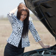 Woman looking under car hood — Stock Photo #9008011