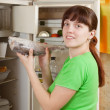 Woman putting  frozen fish into fridge at home — Stock Photo
