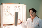 Ophthalmologist with letter table — Foto Stock