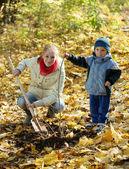 Mujer con hijo restablecimiento de árbol en otoño — Foto de Stock