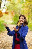 女の子は空気中の葉を投げ — ストック写真