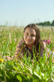 Teen girl lying in meadow — Stock Photo