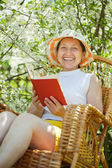 Mature woman relaxing in blossoming garden — Stock Photo