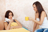 Woman gives cup to unwell friend — Stock Photo