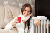 Smiling woman near warm radiator — Stock Photo