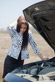 Mujer bajo el capó del coche — Foto de Stock