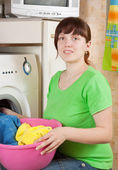 Woman putting clothes in to washing machine — Stockfoto