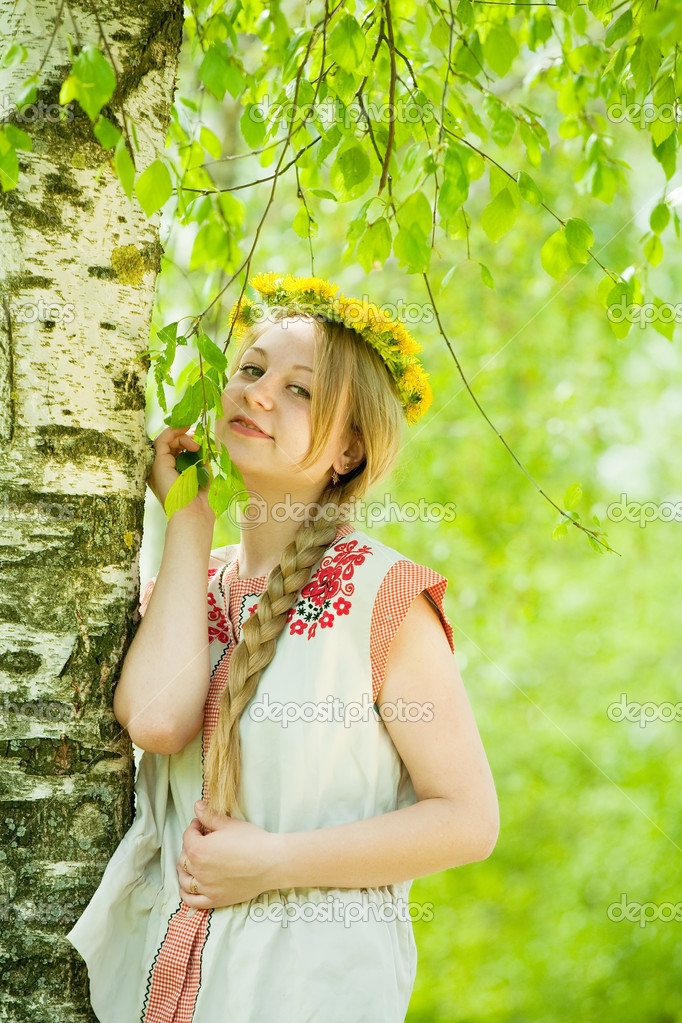 Girl in flowers wreath and traditional clothes near birch — Stock Photo #9004253