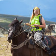 Tourist with backpack on horseback — Stock Photo