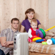 Family at home near oil heater — Stock Photo #9890630