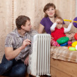 Parents and child  near warm radiator — Stock Photo