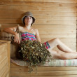 Girl in  sauna with birch flag broom - Foto Stock