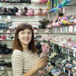 Woman chooses baby shoes — Stock Photo #9891066