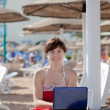Stock Photo: Woman with laptop at resort beach