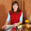 Woman cooking  scomber with cranberry - Foto Stock