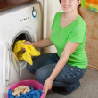 Woman putting clothes in to washing machine - ストック写真