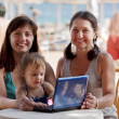 Happy family with laptop at resort — Stock Photo #9891404