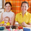Family coloring eggs for Easter holiday — Stock Photo #9891417