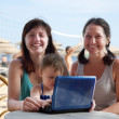 Stock Photo: Women and girl with laptop at beach