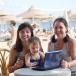 Happy women and  girl   with laptop   at beach — Stockfoto