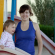 Stock Photo: Happy mother with toddler on slide