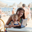 Happy mother and  toddler   with laptop at  beach — Stockfoto