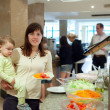 Woman with chid chooses vegetables in buffet — Stock Photo #9891534