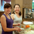 Women takes fresh vegetables in buffet — Stock Photo