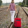 Woman with luggage walking on rail — Stock Photo