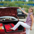 Woman packing her baggage into car — Stock Photo #9891784