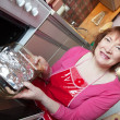 Woman putting scomber into oven — Stock Photo