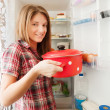 Girl putting pan into refrigerator - Stockfoto