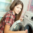 Teen girl loading the washing machine - Foto Stock
