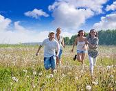 Amigos correndo no prado — Fotografia Stock