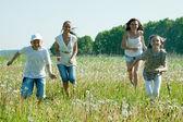 Friends running in meadow — Stock Photo