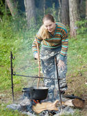 Tourist cooking meal in kettle — Stock Photo