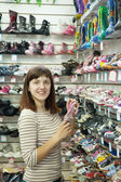 Woman chooses baby shoes — Stock Photo