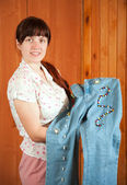 Woman shows jeans beaded by herself — Stock Photo