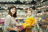 Woman with child chooses baby shoes — Stock Photo