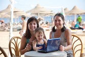 Happy women and girl with laptop at beach — Stock Photo