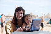 Familia feliz con el portátil en la playa — Foto de Stock