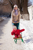 Mother with toddler on sled — Stock Photo