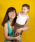 Mother with her child over yellow — Stock Photo