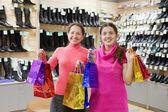 Mujeres con bolsas de compras en la tienda de zapatos — Foto de Stock