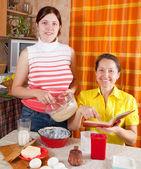 Women making celebration cake — Stock Photo