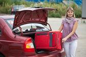 девушка кладет чемодан в автомобиле — Стоковое фото